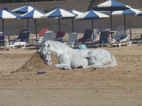 Sand horse sculpture on the beach.