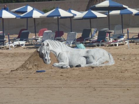 Sand horse sculpture on the beach.