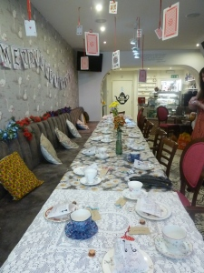 The table was laid with beautiful vintage china. playing cards hung from the ceiling.