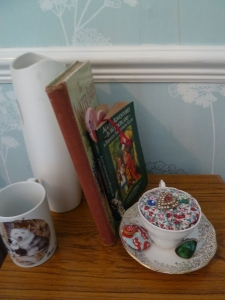A couple of books on my side of the bed and a teacup pincushion. :)