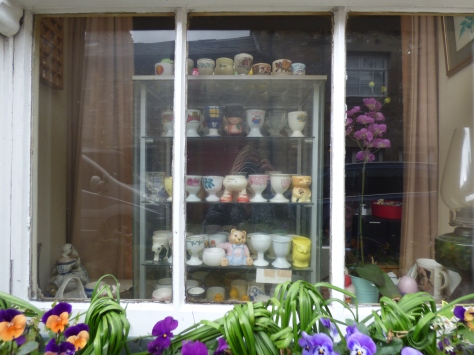An impressive egg cup collection in someone's window.